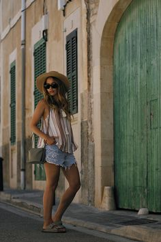 Desi is wearing: striped top with tassels, ripped cut-off denim shorts, Céline trio bag, straw hat, birkenstock sandals - summer holiday look in Santanyí - teetharejade.com