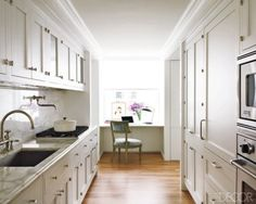 via Elle Decor: white painted cabinets and marble counter/backsplash