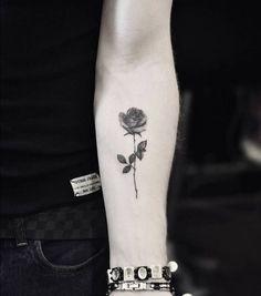 Fine line rose tattoo on the left inner forearm.