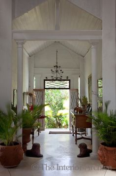 The airy entrance hall opens onto a lush garden and is furnished with palm trees in large terracotta pots
