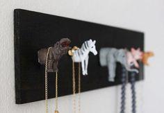 Crie seu próprio organizador com animais de brinquedo, tábua de madeira e cola quente ou parafuso.