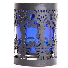 Our tea light holder is made of electric blue glass inside an intricately etched black metal stand, making for a lovely piece of table décor.