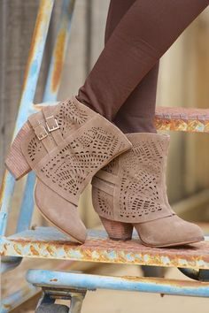 Suede leather perforated,lasercut booties Genuine suede leather is intricately punched with lace-like geometric designs along a slouchy shaft and two silver-b