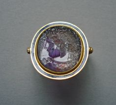 Intaglio; amethyst; winged head of Medusa to right, bent slightly downwards, eyelids drooping; wings in hair and snakes knotted under chin; in gold ring with blue enamel and swivel.