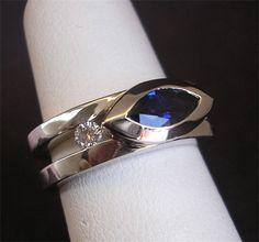 R007 18K WG SAPPHIRE & DIAMOND RING : A striking ring featuring a bezel-set .69 ct Blue Sapphire marquise and two tension-set Diamonds weighing .29 ctw G VS. Gallery Price $4050 Web Price $2825