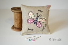 Pink applique butterfly linen pincushion with embroidered words sew, pins and needles handmade by Stitch Galore. www.stitchgalore.com