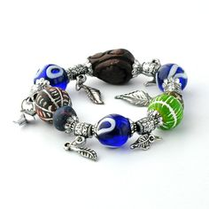 An elasticated Anatolian bracelet comprised of several glass and ceramic ornaments, metal charms and glass beads bearing the Evil Eye symbol.