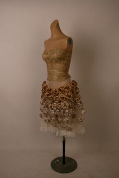 Afternoon Tea Dress. The bodice and the flowers are made entirely of paper, and the skirt is netting, chiffon and lace. The bodice is decorated with text from the Jane Austen Novel 'Pride and Prejudice'. It has a corset effect back that is secured with a champagne coloured ribbon.
