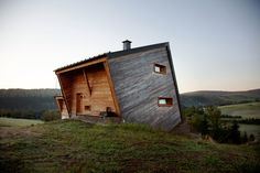 Sebastian Heise's wooden structure, seemingly atilt, overlooks a green valley in Oberwiesenthal, Germany. The two horizontal windows on the side and the front porch give the home its own unique sense of balance.