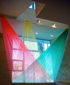 While Gabriel Dawe uses thread to create his ethereal rainbow colored installations, Los Angeles-based artist Megan Geckler uses plastic ribbon or flagging tape. Often used by surveyors to mark spaces on construction sites, the material looks incredibly beautiful when weaved together – whether that be in front of stores, around hallways, or inside shipping containers. …