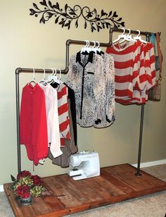 love this clothing rack. bet it would be just as cute made from spray paint PVC pipe and wood pallet for a shabby chic look. <3