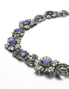Sapphire and diamond necklace, early 20th century Designed as a graduated series of floral motifs, each set to the centre with an oval sapphire, the leaves and petals set with circular-cut and rose diamonds, length approximately 400mm, French import marks.