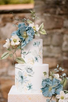 """From the editorial """"Classic Architecture Meets Modern Fine Art Elegance at The Hartwood Stables."""" In keeping with the feminine florals and architectural details, Alex Robba Cake hand-painted blue flowers along with tile that mimicked stone in a modern, yet timeless cake design. The look was topped off with the prettiest sugar flowers that added such grace. 