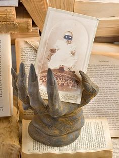Witch's Hand Stand Piles of yellowed paperbacks prop a ceramic witch hand, which clutches a sepia portrait. Photocopy an old picture and draw an eye mask onto it with markers, or print a mask onto an adhesive label and adhere to the photo.