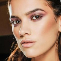 The focus is on her cheeks and eyes.  Her cheeks have been contoured and highlighted giving the cheekbones depth and her eyes are done in a light purple and she has a matted nude lip.