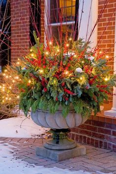 Add lights to decorative urns filled with festive greens for added glow next to your front door. - Traditional Home / Photo: Courtesy of Mariani Landscape