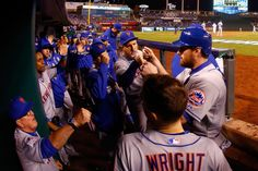 WORLD SERIES GAME 2 - The Mets' Daniel Murphy, right, is greeted by teammates in the dugout after scoring a run on an RBI single by Lucas Duda in the fourth inning against the Kansas City Royals during Game 2 of the World Series at Kauffman Stadium on Oct. 28, 2015. (Photo by Christian Petersen/Getty Images)