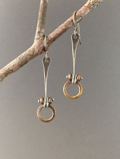 These mixed metal earrings have hammered brass rings suspended below a forged length of sterling silver, pinned into place with a small sterling heat rivet and brass beads. They are simple and elegant. Great lightweight pair to wear every day! Earrings measure approximately 1 3/4 inches long from the top of the earwire to the bottom of the brass ring. Hypo-allergenic titanium earwires. Brushed patina finish. Each pair will vary slightly from those shown here. Larger version also availab...