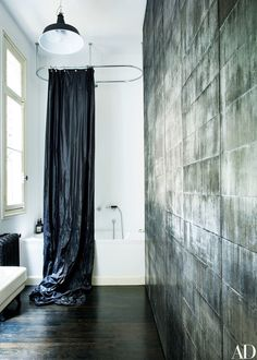 The ball-gown-like shower curtain is made of black sailcloth | archdigest.com