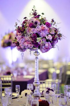 Tall purple centerpiece  Florist: Events in Bloom Photo: Corey Conroy