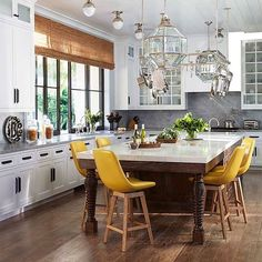Vivid yellow chairs add a bright pop of color to the mostly white kitchen of a breathtaking Malibu oasis. Interior design by @MartynBullard. Photo by Roger Davies.