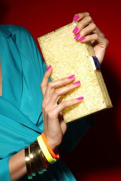 Accessories Trend: Conversation Clutches - Oscar de la Renta's reconstructed amber, poplar and sodalite clutch with Alexis Bittar's 18k gold plated metal bangles and powder coated metal bangles. BCBGeneration's jumpsuit.