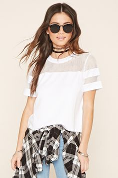 A boxy, athletic-inspired top featuring sheer mesh panels, a round neckline, and striped short sleeves.