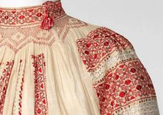 Detail from a traditional Romanian blouse showing a smocked neckline with vibrant red work embroidery broken up with some very fine pulled thread work.