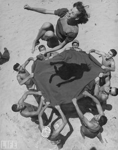 Life Magazine, a group of young men toss a lovely girl up in the air on the beach