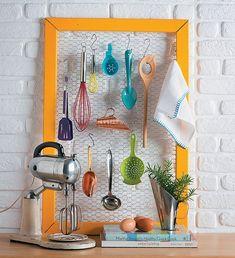 """Concha, batedor, pano de prato e uma infinidade de utensílios cabem no porta-treco improvisado com uma tela de galinheiro e uma moldura. Para os ganchinhos, arames em formato de """"s"""" resolvem a questão. Pintado com uma cor bem viva, como este feito pela loja Acervo à Venda, o quadro vira uma alegria – e uma mão na roda – na cozinha"""