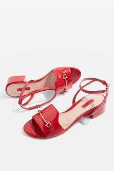 Featuring an adjustable ankle strap and a gold-tone horsebit across the toe band, these gleaming red sandals can't help but make a statement.