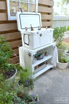 Awesome bar cart and cooler stand for entertaining! Table & Hearth completely transformed this boring, bare, and beat up patio space into a relaxed, neutral, and weathered coastal-meets-farmhouse space! Great DIYs and curated decor make it such a beautiful space.