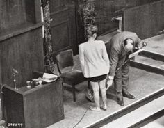Jadwiga Dzido shows her scarred leg to the Nuremberg court as an expert medical witness explains the procedures inflicted on her at Ravensbrück concentration camp, 1942. They were performed by defendants Herta Oberheuser & Fritz Ernst Fischer, Dec. 1946.