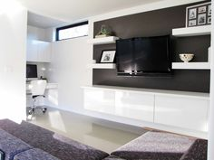 tv mounted on feature wall with floating cupboards and display shelves