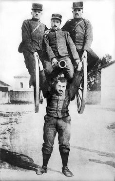 France c. 1917.A strongman in the French Army lifting a cannon overhead along with three of his comrades astride it.