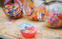 Em baleiros de vidro (Victoria Louças, R$ 6,52 cada), os confeitos ficam acessíveis durante a sessão. Quem quiser levar um pouco mais para seu lugar pode encher as forminhas de cupcakes.
