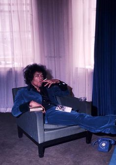 Jimi takes a break from reading to smoke, ponder who let Petra in here, think about whether or not this chair is really and truly blue enough for this room.Jimi Hendrix photographed by Petra Niemeier, 1967.