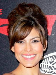 Eva Mendes adds piece-y side-swept bangs and volume on top to modernize her classic French roll.