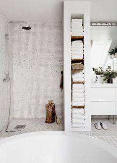 <p>Ici, la cloison qui isole la douche italienne du reste de la salle de bain sert de rangement, une bonne astuce pour optimiser l'espace et agrandir les rangements. La mosaïque blanche, le...