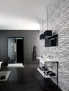 Tile goes very graphic this year, as seen here on the wall behind the sink. Yes, it's neutral, but the combination and pattern make it work as an accent wall. This punctuates an otherwise quiet black, grey and white room designed by Tile of Spain.