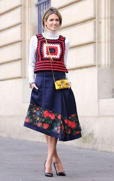 Street style look Helen Bordon com colete de crochet colorido, blusa manga longa gola branca, saia midi  e scarpin preto.