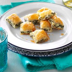 Spanakopita Bites Recipe -For an easy spanakopita, try this version that is made in a pan, then cut into squares. It has all the wonderful taste of the classic version...buttery phyllo with a spinach-cheese filling, but is so simple to do.—Barbara Smith, Chipley, Florida