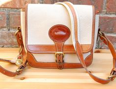 """This striking white and tan pebbled leather crossbody satchel is an original Dooney & Bourke design. It was made in the U.S.A. around the early 1990s.   Features: •  White/Cream pebbled leather exterior with tan trim •  Two-tone white and tan padded leather strap •  1 interior small zip pocket, 4 small slip pockets; 1 back slip pocket w/ brass fastener •  Classic unlined Leather interior •  Original brass duck hang tag •  Solid brass hardware & buckles •  42"""" inch adjustable strap (24"""" strap…"""