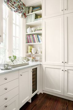 Shaker-style cabinets mixed with open shelves (for cookbooks and dishes) provide plenty of storage. The timeless look of the white palette ensures the homeowners will enjoy the space for many years to come.