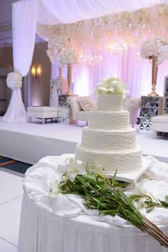 "White buttercream wedding cake | Krishna and Heren's romantic ""Snow White"" wedding reception with cascading orchids, white roses and hydrangeas and metallic accents 