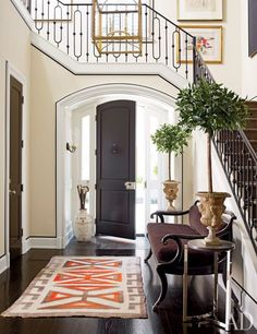 Custom-made moldings amplify the elegance of the entrance hall, which contains a Regency settee and a 1920s Navajo rug; the sconce is by Vaughan, and the umbrella stand is a Ming-dynasty sake jar. The art displayed along the stairway includes a colorful work on paper by Joan Mitchell.