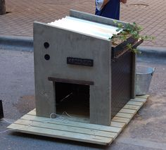 Dog house with planter that is designed to allow rain water to run directly into the plants