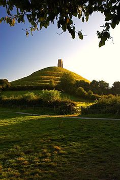 Since the alleged discovery of Arthur and Guinevere's remains in the century, it has been claimed that Glastonbury Tor stands on the site of ancient Avalon. Once surrounded by marshland, it was virtually an island during the Dark Ages. Glastonbury Tor, Glastonbury England, Glastonbury Somerset, Legend Of King, King Arthur Legend, Roi Arthur, Stonehenge, British Isles, Historical Sites