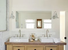 Barn wall sconces in the Concord Green Healthy Home light up this crisp and clean vanity.