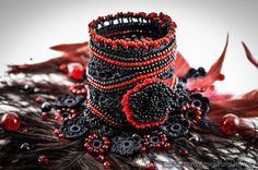 This stylish cuff is crochet from black mercerized cotton thread with resistant colors. It is decorated with black and red seed beads and